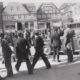 En stor skare af tilkskuere modtager og følger tyske tropper på Torvet